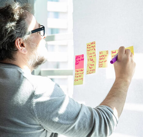 man with glasses writting on sticky notes